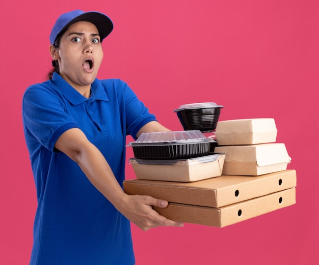Erschrockenes junges liefermädchen, das uniform mit kappe trägt, die lebensmittelbehälter auf pizzaschachteln an der seite lokalisiert auf rosa wand heraushält