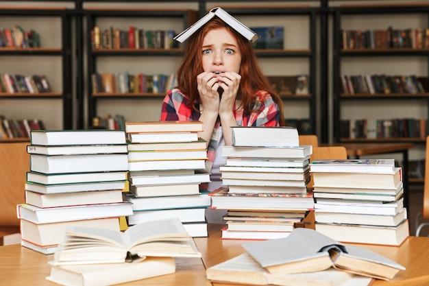 Erschrockenes junges mädchen, das an der bibliothek sitzt