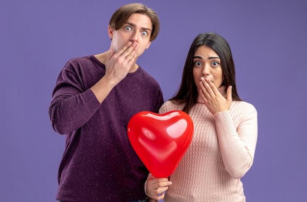 Erschrockenes junges paar am valentinstag, das mit einem herzballon bedeckten mund mit den händen isoliert auf blauem hintergrund hält