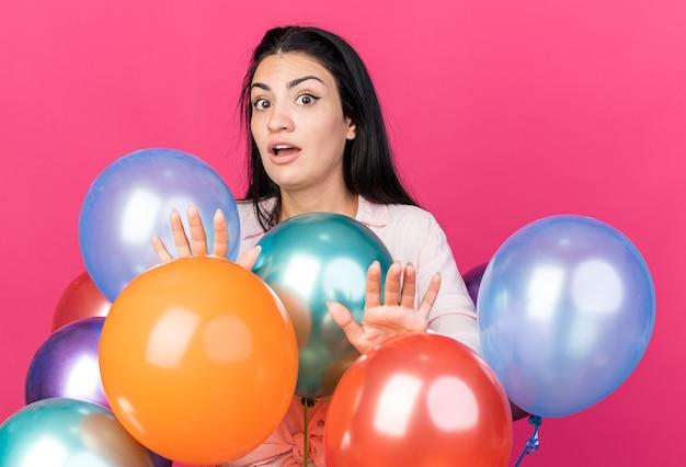 Erschrockenes junges schönes mädchen, das hinter ballons steht und händchen an der kamera hält