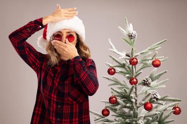 Erschrockenes junges schönes mädchen, das in der nähe des weihnachtsbaums steht und eine weihnachtsmütze mit brille trägt, bedeckt den mund mit der stirn mit den händen isoliert auf weißem hintergrund