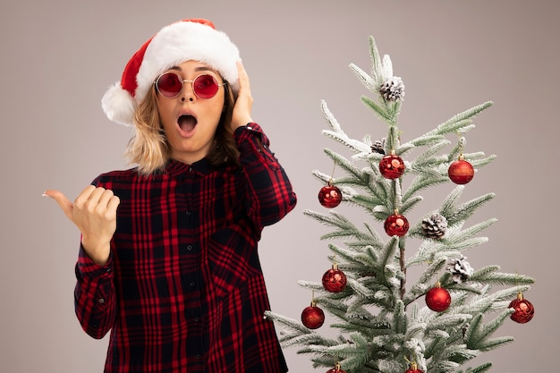 Erschrockenes junges schönes mädchen, das in der nähe des weihnachtsbaums steht und weihnachtsmütze mit brille trägt, zeigt seitlich auf weißem hintergrund mit kopierraum