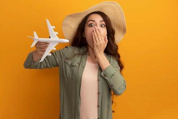 Erschrockenes junges schönes mädchen, das olivgrünes t-shirt und hut hält, die spielzeugflugzeug bedeckten mund mit hand lokalisiert auf gelber wand halten