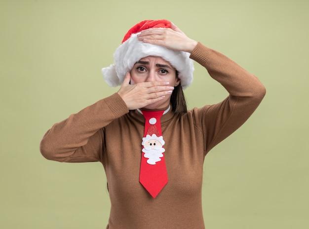 Erschrockenes junges schönes mädchen, das weihnachtshut und krawatte bedecktes gesicht mit hand lokalisiert auf olivgrünem hintergrund trägt