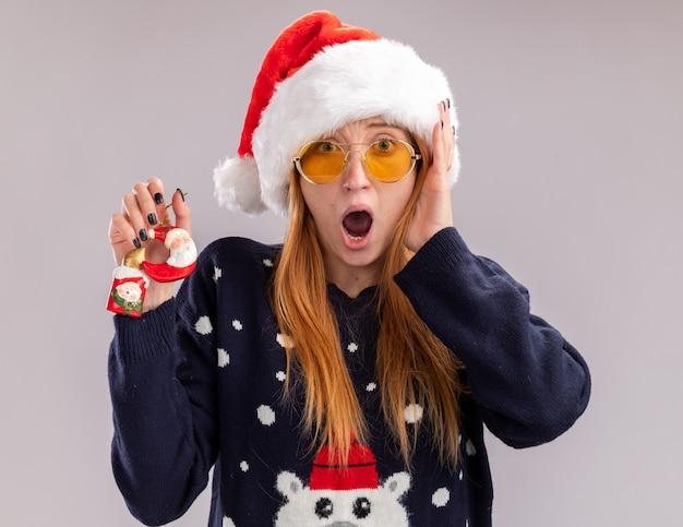 Erschrockenes junges schönes mädchen, das weihnachtsmütze und brille hält, die weihnachtsspielzeug hält hand auf wange lokalisiert auf weißem hintergrund hält
