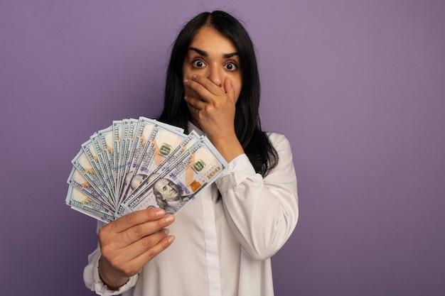 Erschrockenes junges schönes mädchen, das weißes t-shirt hält, das geld bedeckte mund mit hand lokalisiert auf purpur mit kopienraum hält