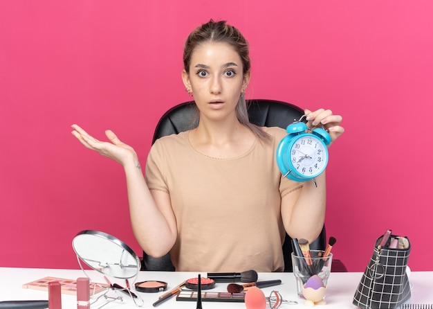 Erschrockenes junges schönes mädchen sitzt am tisch mit make-up-tools, die den wecker einzeln auf rosafarbenem hintergrund halten