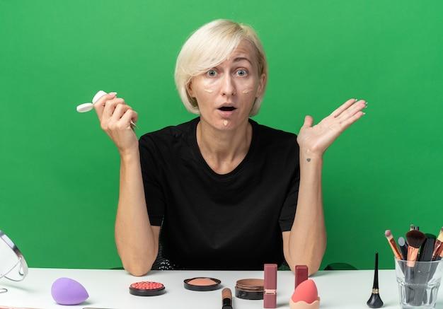 Erschrockenes junges schönes mädchen sitzt am tisch mit make-up-tools, die ton-up-creme auftragen, die hände einzeln auf grünem hintergrund ausbreitet