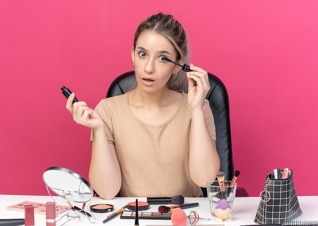Erschrockenes junges schönes mädchen sitzt am tisch mit make-up-tools, die wimperntusche auf rosa hintergrund auftragen