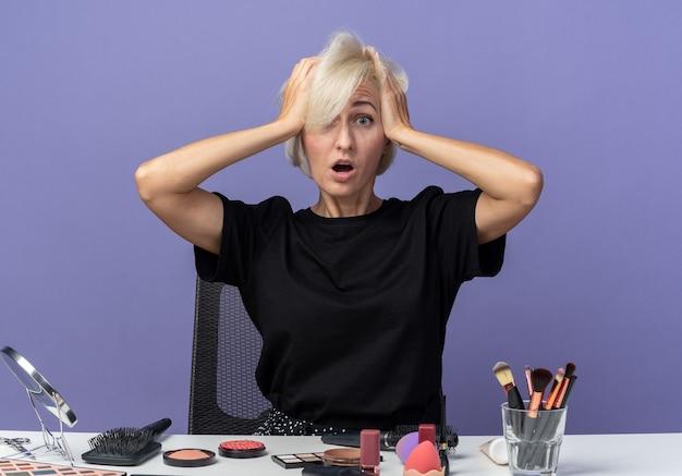 Erschrockenes junges schönes mädchen sitzt am tisch mit make-up-tools packte den kopf isoliert auf blauem hintergrund