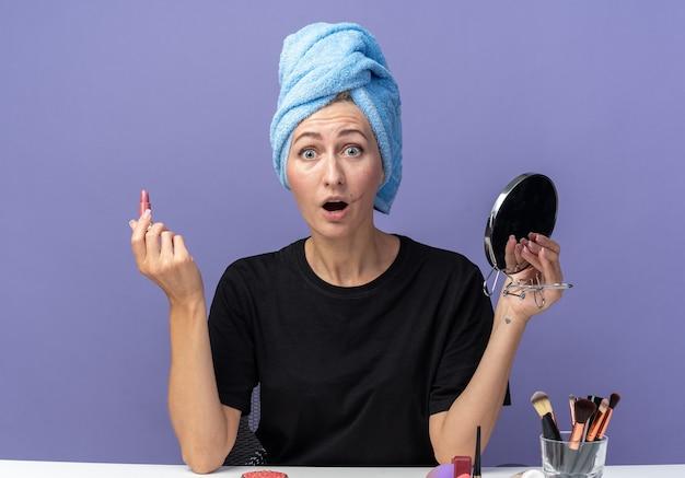 Erschrockenes junges schönes mädchen sitzt am tisch mit make-up-tools und wischt sich die haare im handtuch ab und hält lippenstift mit spiegel isoliert auf blauem hintergrund