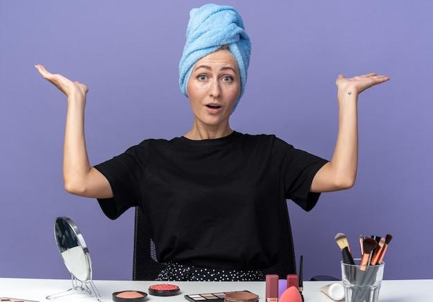 Erschrockenes junges schönes mädchen sitzt am tisch mit make-up-werkzeugen und wischt sich die haare im handtuch ab und verteilt die hände einzeln auf blauem hintergrund