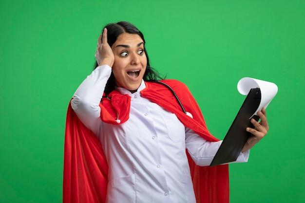 Erschrockenes junges superheldenmädchen, das medizinisches gewand mit stethoskop hält und die zwischenablage betrachtet, die hand auf kopf lokalisiert auf grün setzt