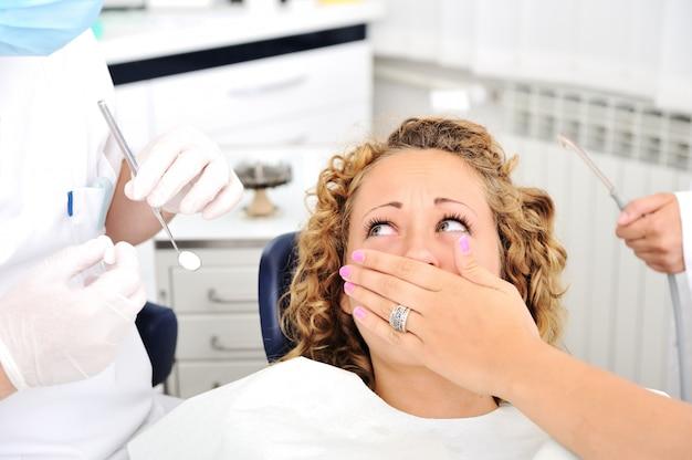Erschrockenes mädchen an der zahnüberprüfung des zahnarztes