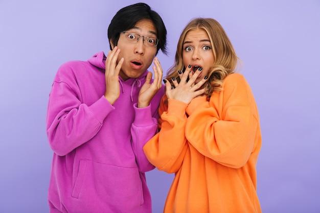 Erschrockenes multhiethnisches teenagerpaar, das isoliert zusammen steht und schaut