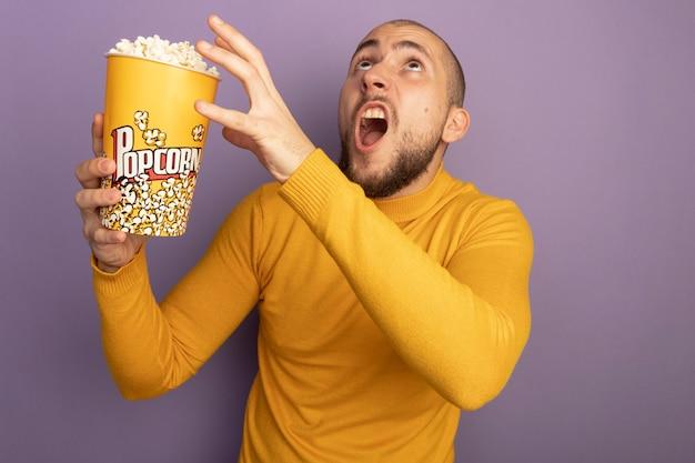 Erschrockenes nachschlagen junger hübscher kerl, der eimer popcorn lokalisiert auf lila wand hält