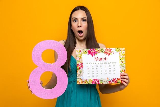 Erschrockenes schönes junges mädchen am glücklichen frauentag, der kalender mit der nummer acht hält
