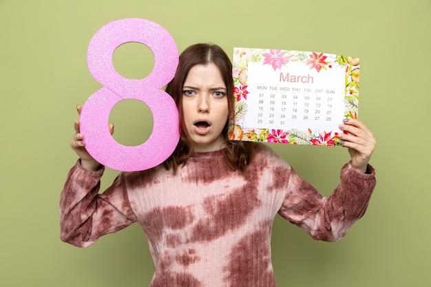 Erschrockenes schönes junges mädchen am glücklichen frauentag, der nummer acht mit kalender um gesicht hält