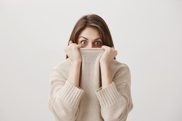 Erschrockenes schüchternes mädchen, das gesicht im pulloverkragen versteckt und alarmiert