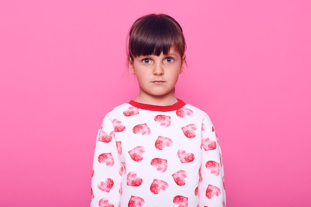 Erschrockenes vorschulkindmädchen, das kamera mit großen augen voller angst betrachtet, lässige kleidung tragend, dunkelhaariges weibliches kind mit schockausdruck, isoliert über rosa wand.