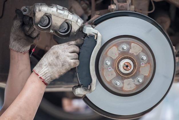 Ersetzen der bremsbeläge im servicecenter der automechaniker mit weißen handschuhen ist dabei, die bremsbeläge des autos zu wechseln