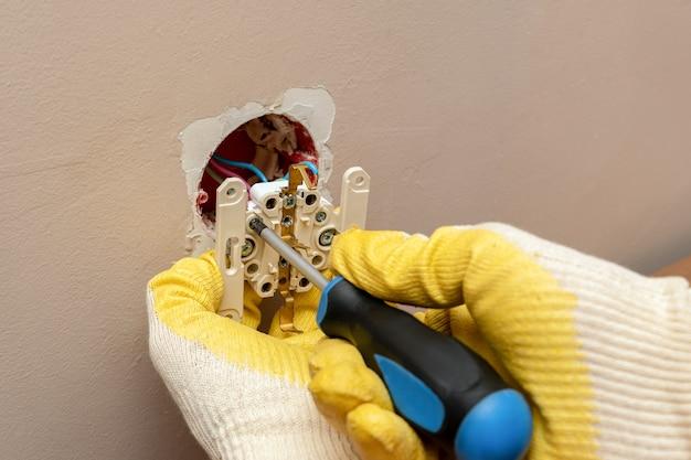 Ersetzen, installieren einer steckdose, steckdose mit den händen in gummischutzhandschuhen