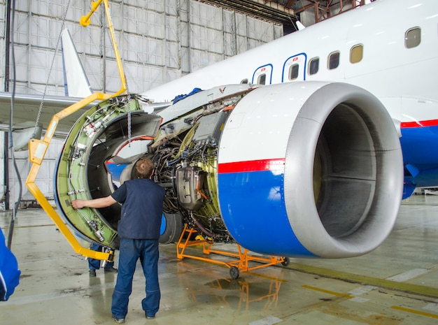 Ersetzen sie den motor im flugzeug, tippen arbeitende menschen. konzeptwartung von flugzeugen.