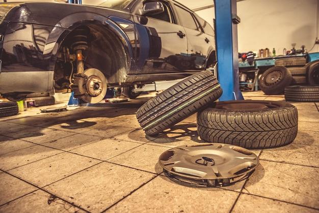 Ersetzen von winterreifen auf sommerreifen in einer fachwerkstatt mit hilfe von fachwerkzeugen. auto auf einem hydraulischen wagenheber
