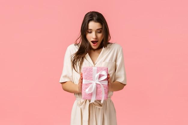 Erstaunen, feiern und feiertagskonzept. überraschte freundin hält box des geschenks, nicht erwartet geschenk erhalten, offener mund fasziniert blick berührt verpackte box, rosa hintergrund