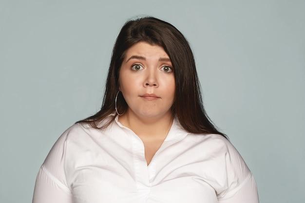 Erstaunen, überraschung, schock und erstaunen. attraktive emotionale junge brünette mitarbeiterin mit übergewicht, die einen schockierten gesichtsausdruck erschreckt hat, während sie von ihrem wütenden chef gerügt wird