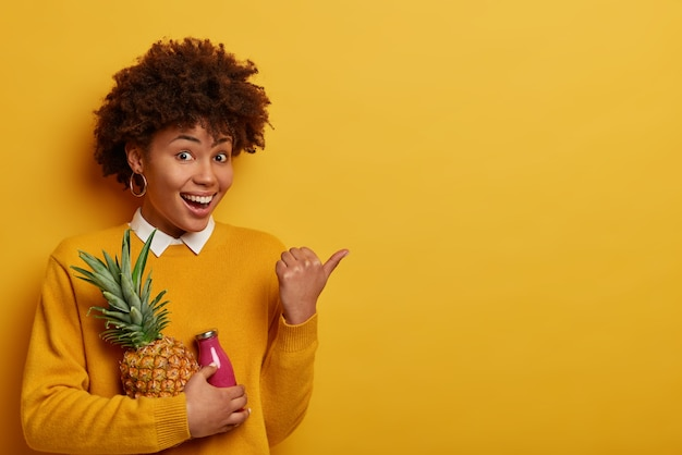Erstaunlich erfreute frau hat gute laune, hält frische ananas und eine flasche smoothie, zeigt mit dem daumen auf den kopierraum, hält sich an die diät, isst obst mit vielen vitaminen, trägt gelbe kleidung