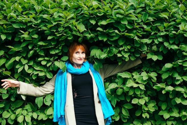 Erstaunlich fröhliches rotes haarmädchen im schwarzen kleid, im hellen mantel und im großen blauen schal fällt in großen grünen busch mit kopienraum auf grün.