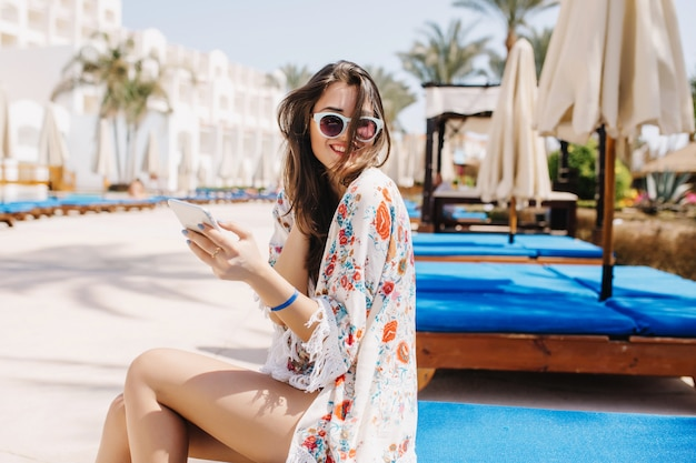 Erstaunlich gebräuntes mädchen mit dunklem lachendem haar, das auf blauem bockbett nahe dem pool sitzt. wunderschöne brünette junge dame im stilvollen hemd mit blumenverzierung, die ihr telefon hält und zu jemandem lächelt