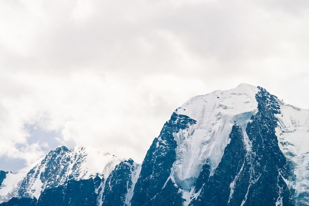 Erstaunlich große gletscheroberseite. schneebedeckte bergkette im bewölkten himmel. wunderbarer riesiger felsiger kamm mit schnee im nebel. atmosphärische minimalistische landschaft majestätischer natur des hochlands. ruhige berglandschaft.