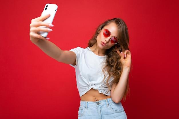 Erstaunlich schöne junge blonde frau, die ein handy hält und ein selfie-foto mit dem smartphone macht