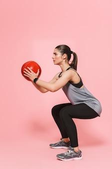 Erstaunlich schöne junge hübsche fitness-frau macht sportübungen mit ball isoliert über rosa wand