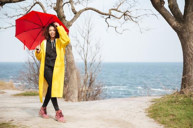 Erstaunliche afrikanische lockige junge dame, die gelben mantel trägt