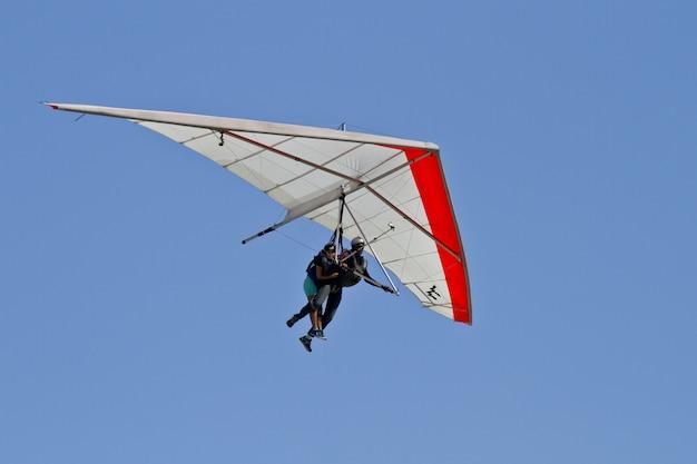 Erstaunliche ansicht des menschlichen fliegens auf einem hängegleiter lokalisiert auf einem blauen himmelhintergrund