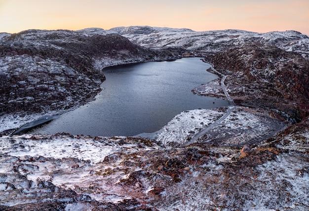 Erstaunliche arktische landschaft mit einer hochgelegenen gefrorenen see-eis-winterstraße durch die tundra-hügel in teriberka