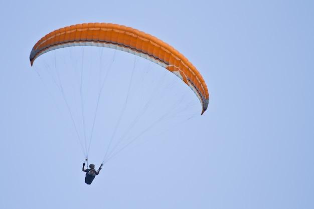 Erstaunliche aufnahme eines menschlichen gleitschirms auf blauem himmel
