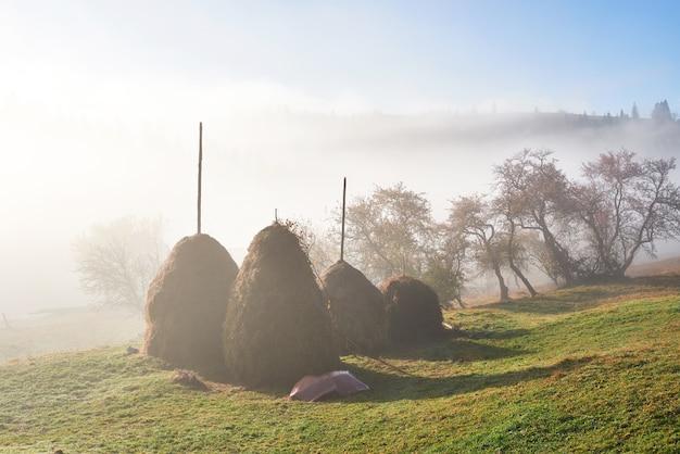 Erstaunliche berglandschaft mit nebel und heuhaufen im herbst