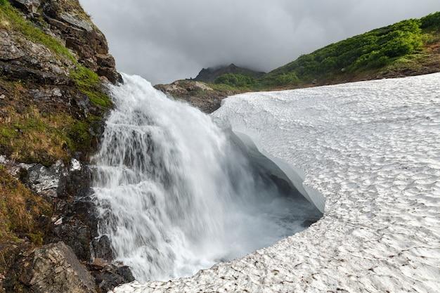 Erstaunliche berglandschaft sommeransicht des wasserfalls, der in das schneefeld im gebirge fällt
