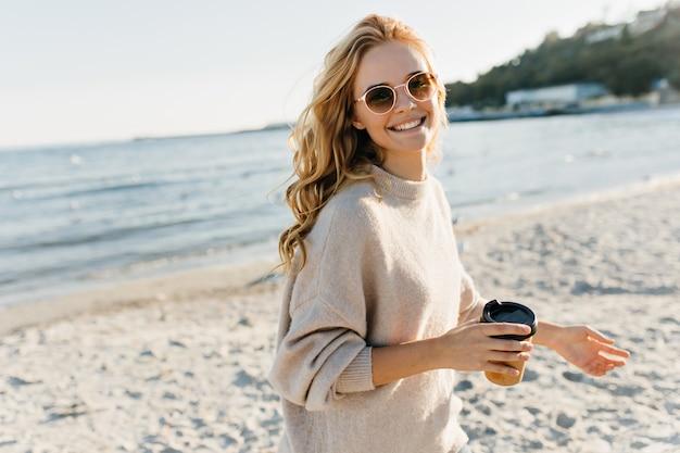 Erstaunliche blinde frau, die tasse kaffee im strand hält. enthusiastisches weibliches modell in der sonnenbrille, die nahe see am kalten tag aufwirft.