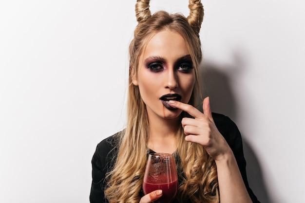 Erstaunliche blonde frau, die an halloween-partei mit blut aufwirft. charmanter vampir mit schwarzem make-up.
