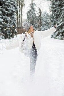 Erstaunliche blonde frau, die mit schnee im wald spielt