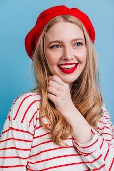 Erstaunliche blonde frau, die positive gefühle ausdrückt. trendiges mädchen in französischer baskenmütze auf blauer wand.