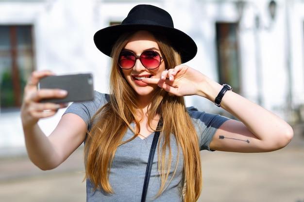 Erstaunliche blonde frau, die selfie auf der straße macht
