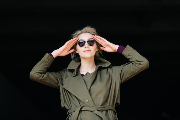 Erstaunliche blonde frau mit grünem mantel