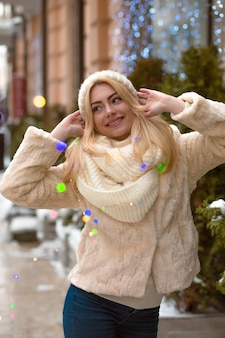 Erstaunliche blonde frau mit weißer strickmütze und schal, die im winter mit bunter girlande posiert