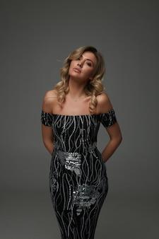 Erstaunliche blondine mit langer lockiger frisur und natürlichem make-up, das im studio für modemagazin schießt. trägt ein schwarzes partykleid mit glitzern und schuhen mit hohen absätzen. professionelles model, wunderschöne dame